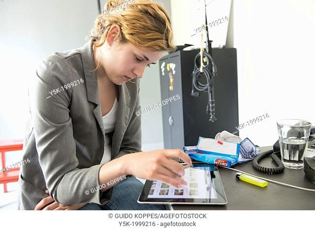 Tilburg, Netherlands. Studio-portrait of a young woman, working on her Digital Tablet, viewing images on the AGE FotoStock website