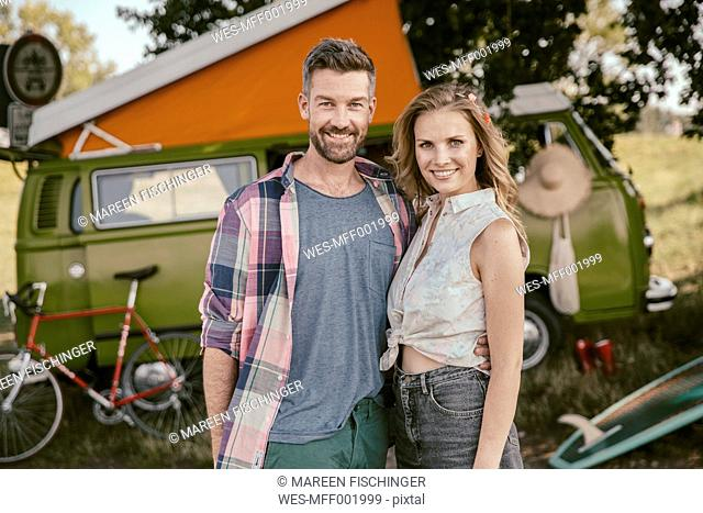 Smiling couple in front of van in the nature