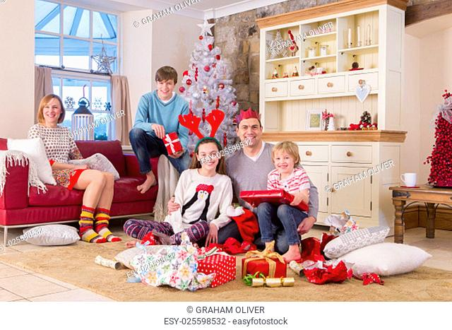 Two generation family in front of a christmas tree opening presents. They are all dressed for christmas and smiling at the camera