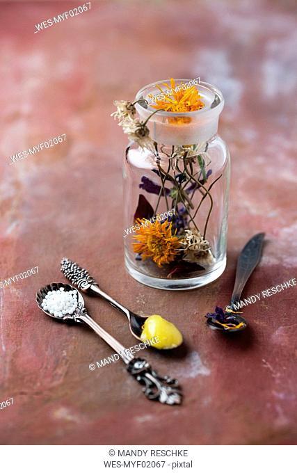 Blossoms of medical plants, medicine flask, marigold salve and globules