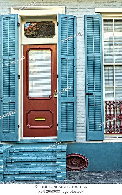 New Orleans, LA, French Quarter. Close Up of Entry Door and Shuttered Window on a Small, Pastel Painted Home