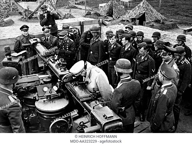 Hermann Goering inspecting a base of the German Air Force. Hermann Goering looking through a telemeter surrounded by soldiers during an inspection of a base of...