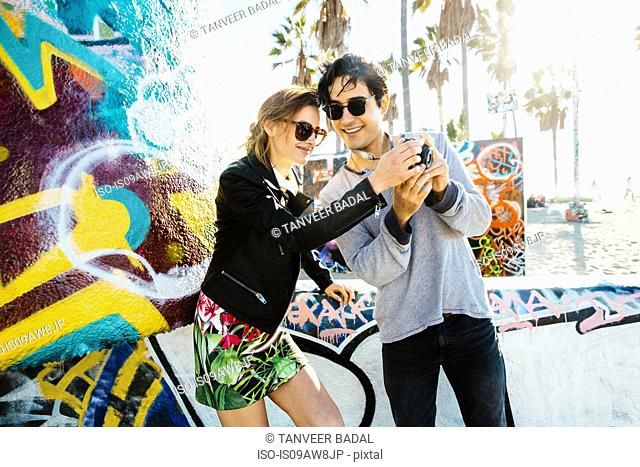 Young couple standing by graffiti art, looking at back of digital camera