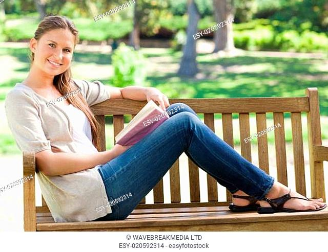 Side view of a smiling woman with her book sitting on a park bench