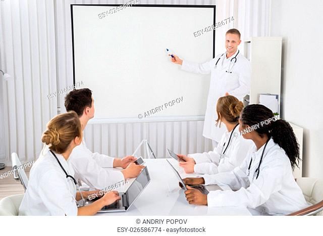Young Male Doctor Pointing At Blank Board In Front Of His Colleagues