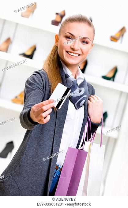 Woman showing credit card in footwear shop with great variety of stylish shoes