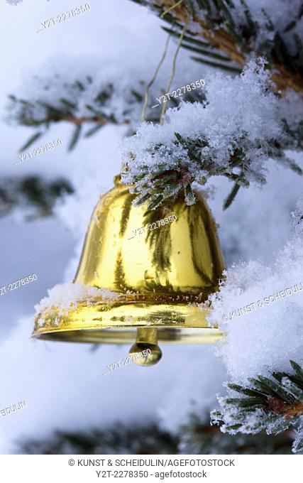 Christmas bell hanging in a snow-covered fir tree