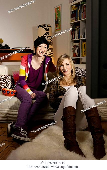 two young women sitting in living room watching television