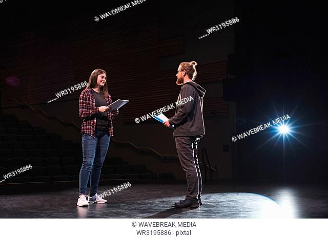 Male and female actress reading script on stage