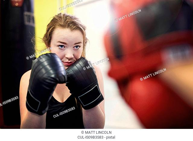 Young female boxer poised to box punch mitt