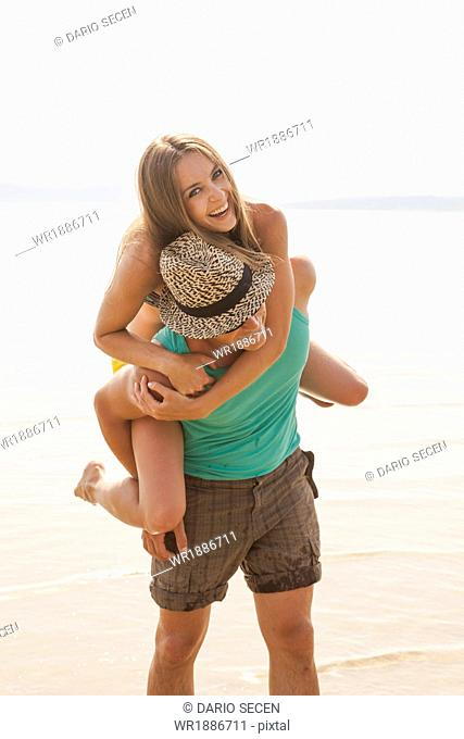 Croatia, Young couple on beach fooling about