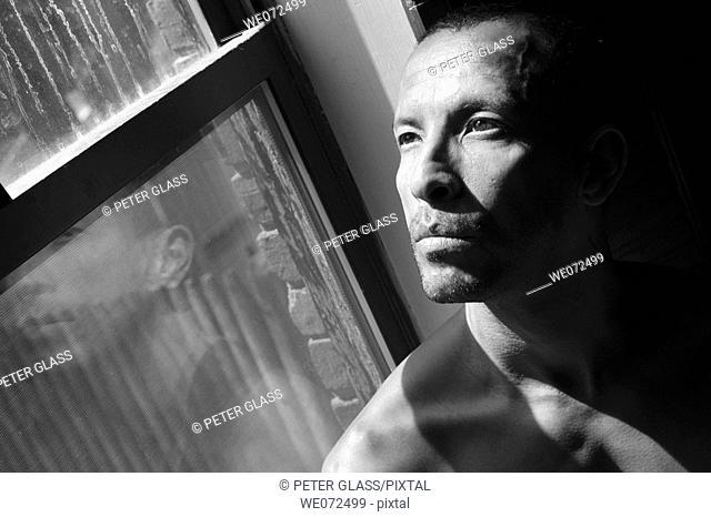Hispanic man posing by his window