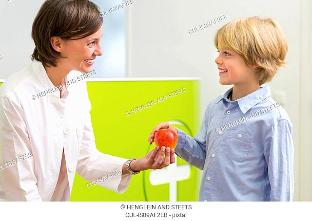 Dentist giving boy apple in dental reception
