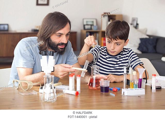 Father and son working on science experiment at home