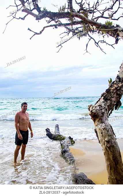 handsome caucasian man in his bathing suit in his 30's 40's 50's with feet in the paradise water of the Beautiful white beaches on Red Frog Beach Resort where...