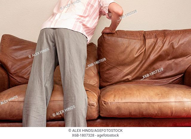 Man looking for lost item behind sofa cushions