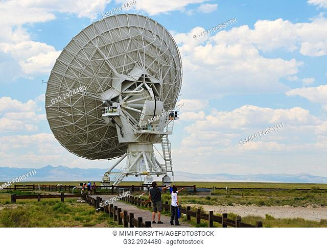 one unit of Very Large Array radio telescope facility, New Mexico, listening for space communication. People give sense of scale