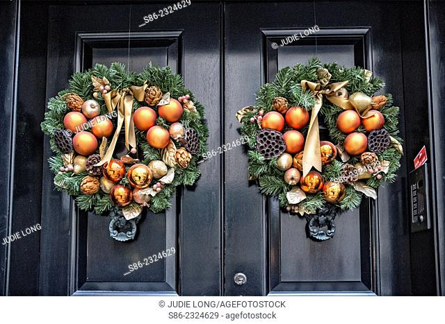 Pair of Christmas Decorative Wreaths, with gold balls, pine cones and bows, mounted on the double doors of a New York City Town House