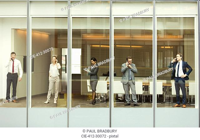 Business people talking on cell phones and reviewing paperwork at conference room window