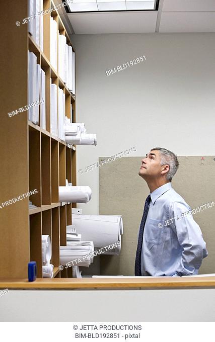 Caucasian businessman looking for blueprints