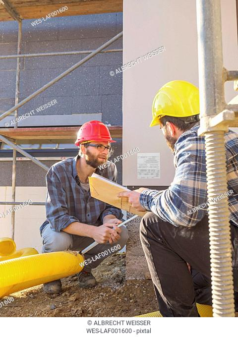 Two craftsmen discussing in construction site