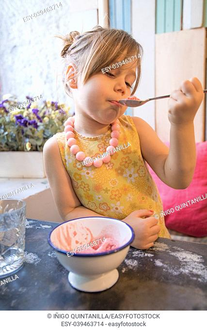 Three years old blonde little girl with yellow dress an necklace eating and enjoying strawberry ice cream with spoon from bowl, sitting indoor in restaurant