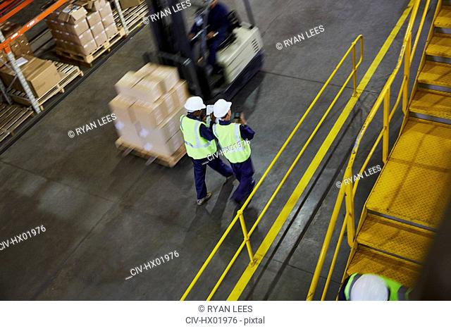Forklift and workers on the move in distribution warehouse