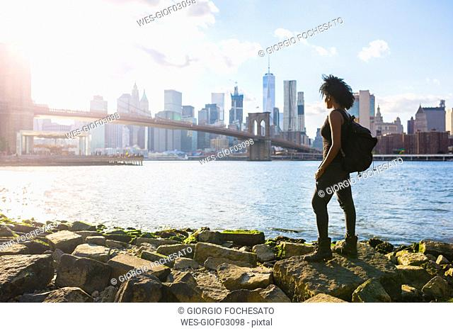 USA, New York City, Brooklyn, woman standing at the waterfront