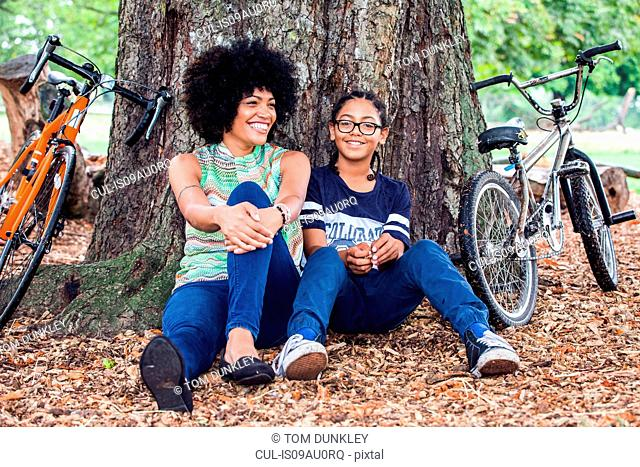 Portrait of mature woman and son sitting against park tree