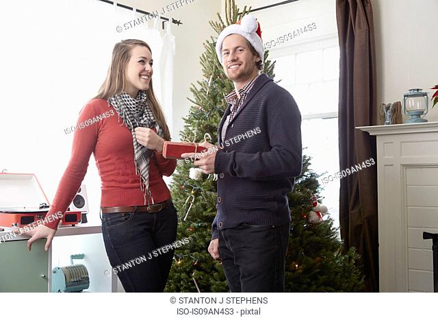 Young man in santa hat holding christmas gift for girlfriend