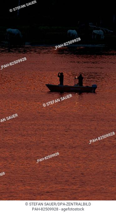 Two anglers in a boat at sunset off the island of Usedom in the Baltic Sea near Wolgast, Germany, 4 August 2016. PHOTO: STEFAN SAUER/DPA   usage worldwide