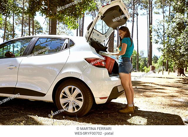 Smiling young woman loading a car