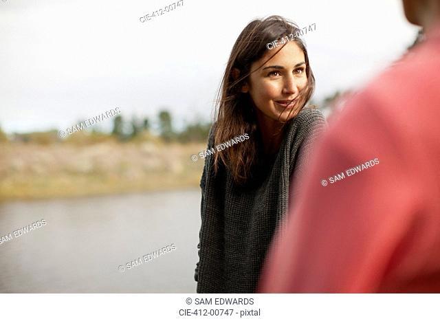 Smiling woman looking at man at lakeside