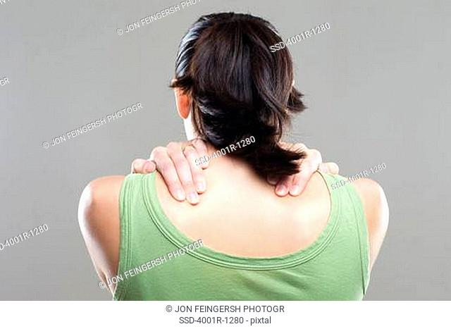 Rear view of a young woman suffering from neckache