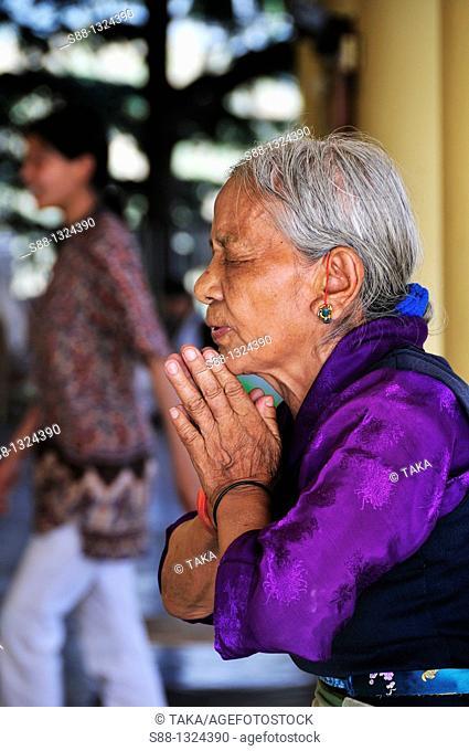 Woman pray in the Tibetan monastery