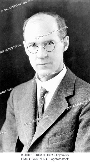 A chest up portrait of Alexander Graham Christie wearing a suit at 29 years of age, 1920