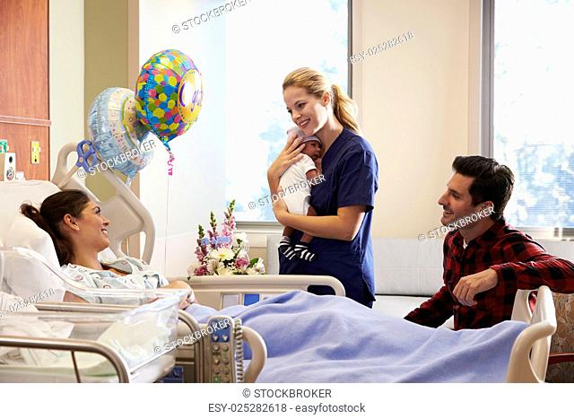 Family And Nurse With New Born Baby In Post Natal Department