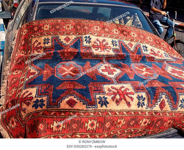 Oriental carpets in a flea market for display on a car
