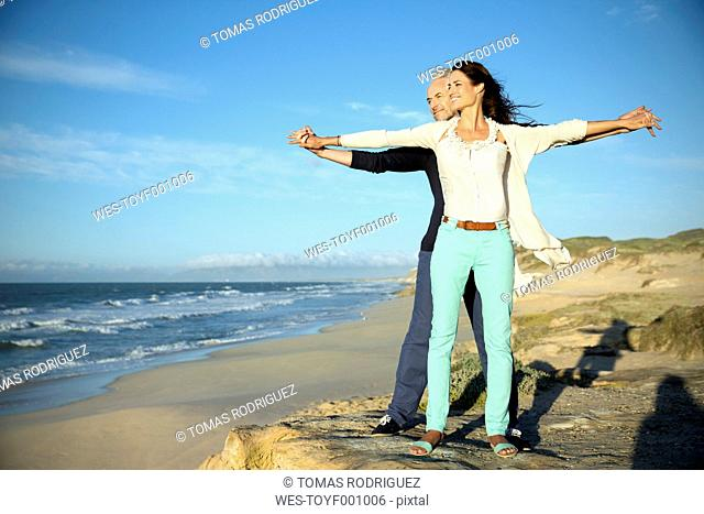 South Africa, couple with outstretched arms standing on the beach looking at distance