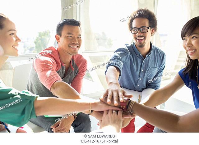 Creative business people connecting hands in huddle
