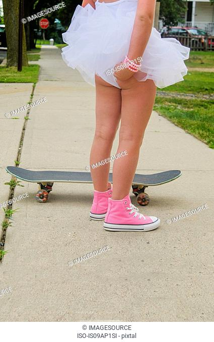 Young girl standing next to skateboard, adjusting tutu, rear view, low section