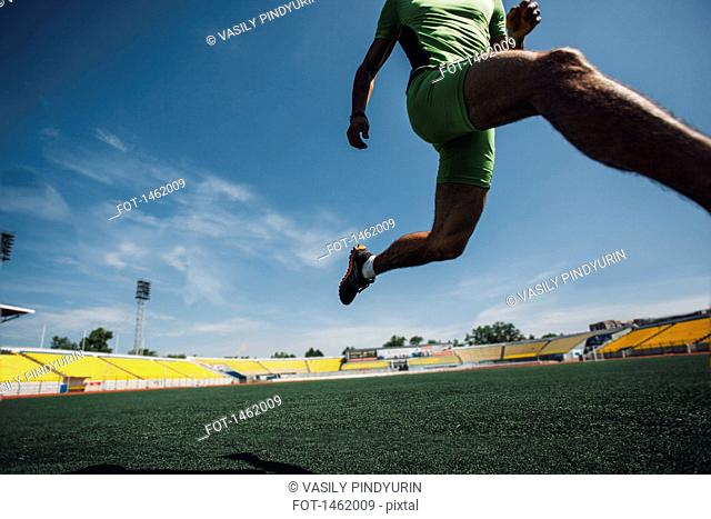 Low section of young male athlete running on field in stadium
