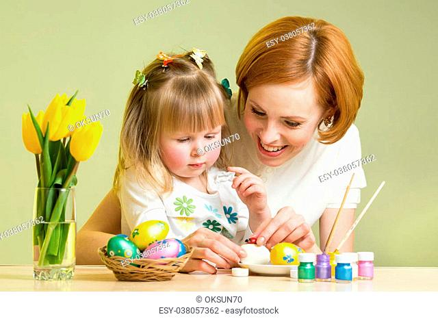 happy mother teaches child daughter to decorate Easter eggs