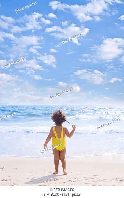 Hispanic girl standing on beach