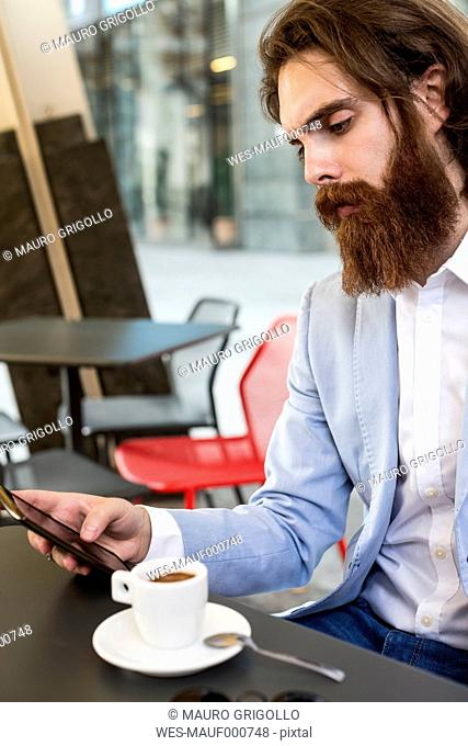 Stylish businessman using cell phone in a cafe