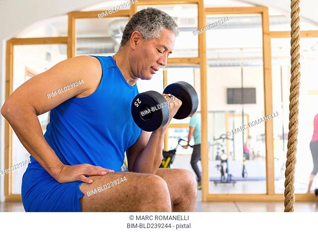 Mixed Race man curling dumbbell in gymnasium