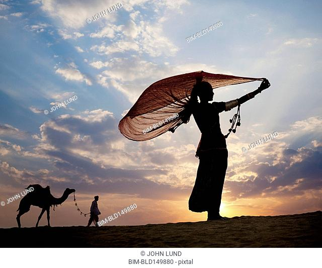 Men outdoors with camel at sunset