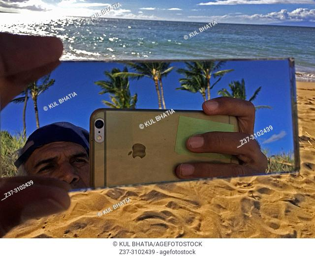 A man combines the sea, the sand, and the trees in a selfie on the beach, Maui, Hawaii, USA
