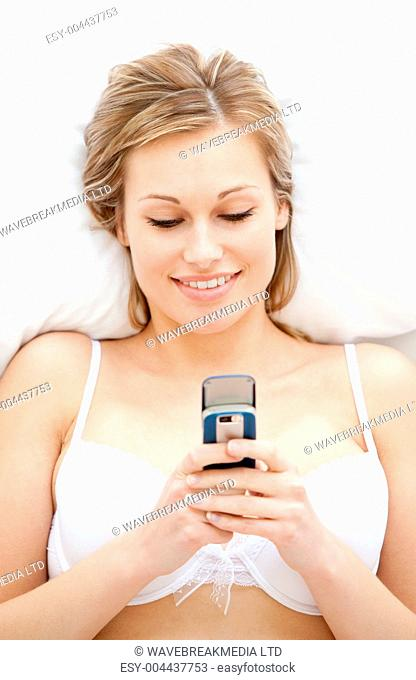 Smiling woman in underwear sending a text