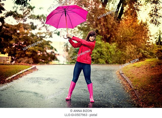 Young woman holding pink umbrella in a park, Debica, Poland